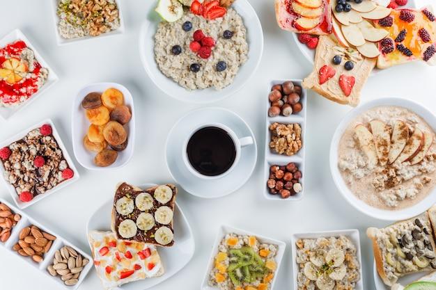 Aveia com frutas, nozes, geléia, café, sanduíche de frutas, leite, canela, damascos secos em pratos