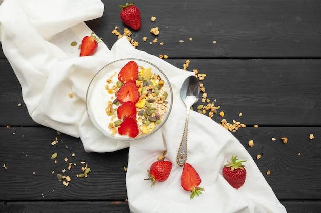 Aveia com iogurte e frutas em um preto de madeira. vista do topo. café da manhã saudável.