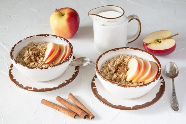Aveia com maçã e canela, leite em um belo prato de cerâmica em uma mesa branca. alimentação saudável. uma dieta rica em fibras. estilo de vida saudável
