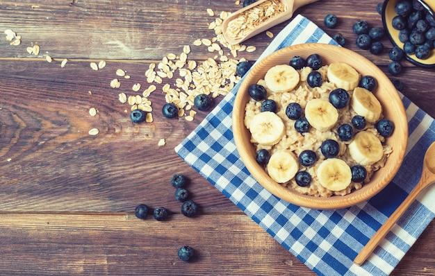 Aveia com mirtilos e banana em uma tigela de madeira com fundo de madeira rústica. café da manhã saudável. vista do topo.