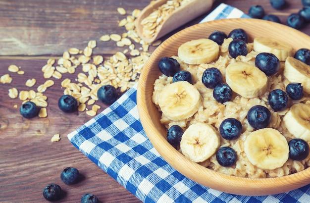 Aveia com mirtilos e banana em uma tigela de madeira com fundo de madeira rústica. café da manhã saudável.