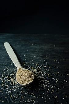 Aveia em flocos do trigo em uma colher de madeira em um fundo escuro de madeira.