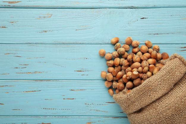 Avelãs, avelã em saco de estopa em pano de fundo azul de madeira. fundo de avelã, comida saudável. vista do topo