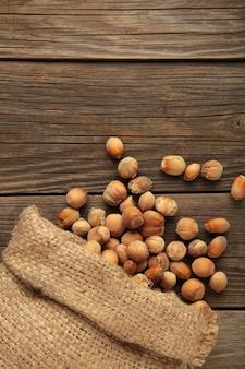 Avelãs, avelã em saco de estopa em pano de fundo cinza de madeira. fundo de avelã, comida saudável. foto vertical