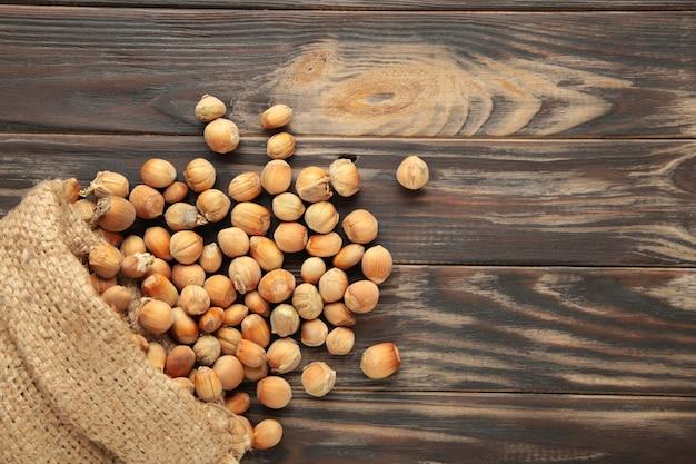 Avelãs, avelã em saco de estopa em pano de fundo de madeira marrom. fundo de avelã, comida saudável. vista do topo