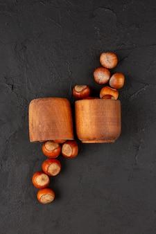 Avelãs de vista superior dentro de panelas marrons no chão escuro