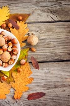 Avelãs e nozes em uma tigela em uma das folhas de outono