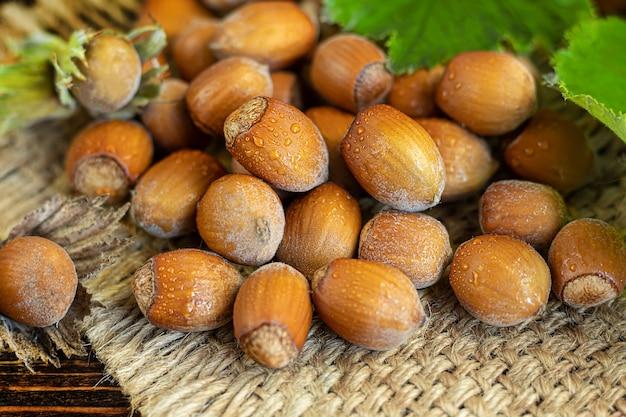Avelãs em um fundo de madeira com folhas verdes. contém vitaminas e minerais benéficos.