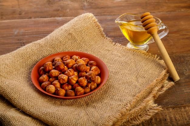 Avelãs em um prato na sacaria ao lado de mel com uma colher sobre uma mesa de madeira.