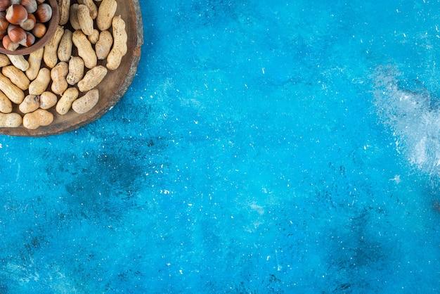Avelãs em uma tigela a bordo com amendoim na superfície azul