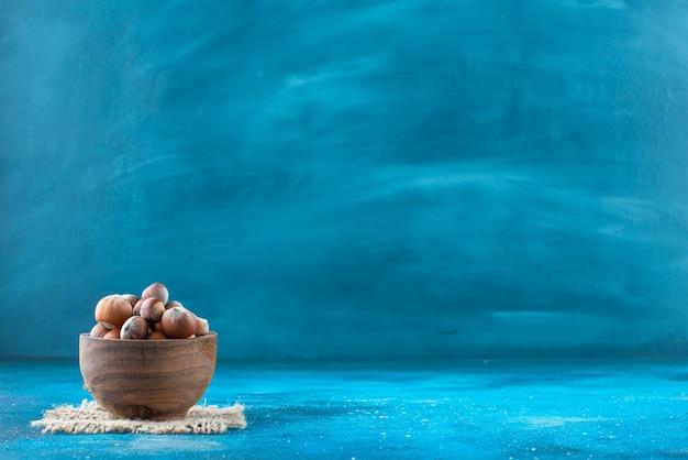 Avelãs em uma tigela com textura na superfície azul