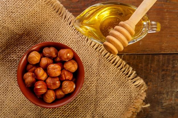 Avelãs em uma tigela em um saco ao lado de mel com uma colher em uma mesa de madeira foto horizontal