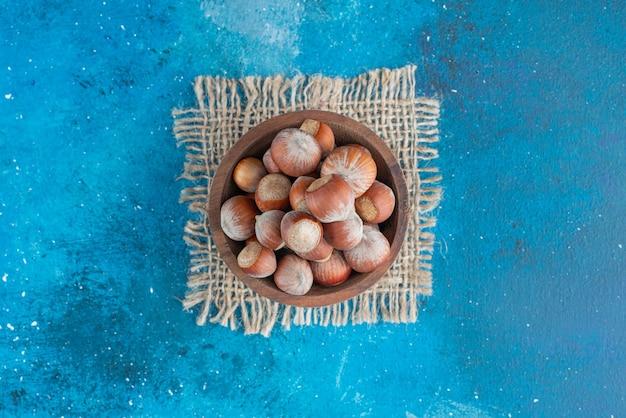 Avelãs em uma tigela na textura, na mesa azul.