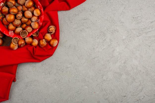 Avelãs frescas inteiras e descascadas sobre um tecido vermelho e um piso leve