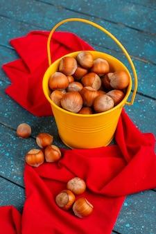 Avelãs inteiras frescas dentro de uma cesta amarela no azul