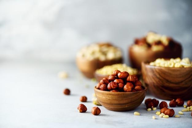 Avelãs na tigela de madeira. variedade de nozes - castanha de caju, avelãs, nozes, pistache, nozes, pinhões, amendoim, passas.