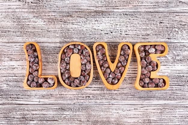 Avelãs sem casca plana leigos no prato em forma de amor na mesa de madeira