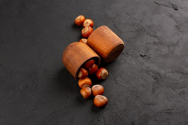 Avelãs vista frontal dentro de panelas marrons no chão escuro