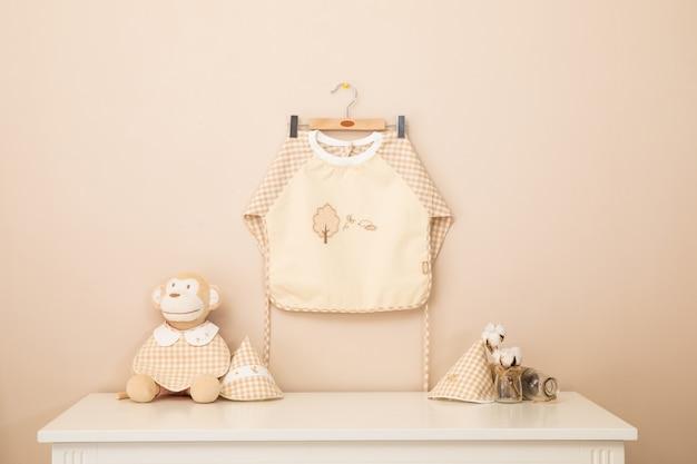 Avental de bebê e colthes do bebê estão lavando e secando nas barras da cremalheira.