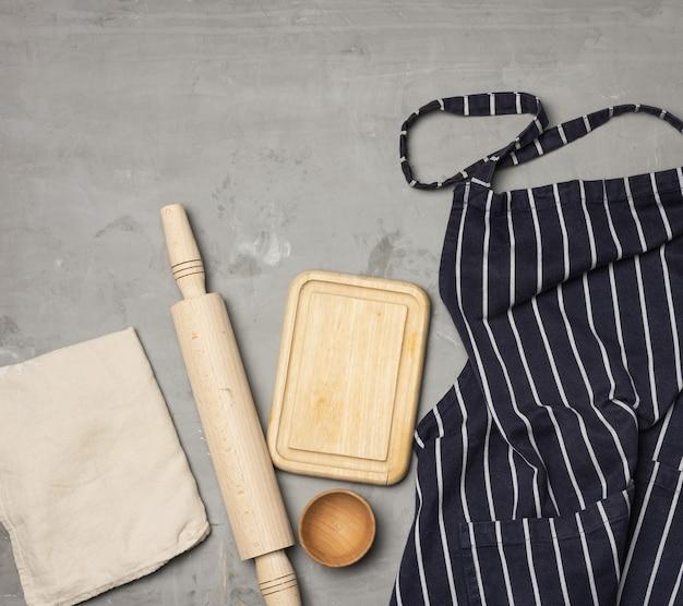 Avental de chef listrado de azul, utensílios de madeira na superfície cinza, vista superior