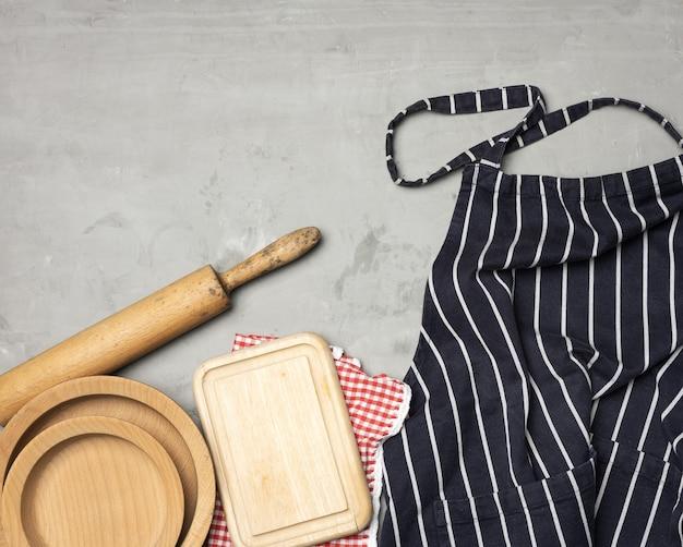Avental de chef listrado em azul, utensílios de madeira, vista superior
