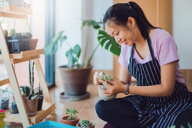 Avental vestindo da jovem mulher asiática que importa-se com a planta interna verde em casa.