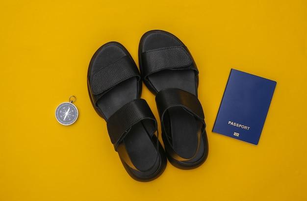Aventura, conceito de viagens. sandálias, bússola e passaporte em um fundo amarelo. postura plana