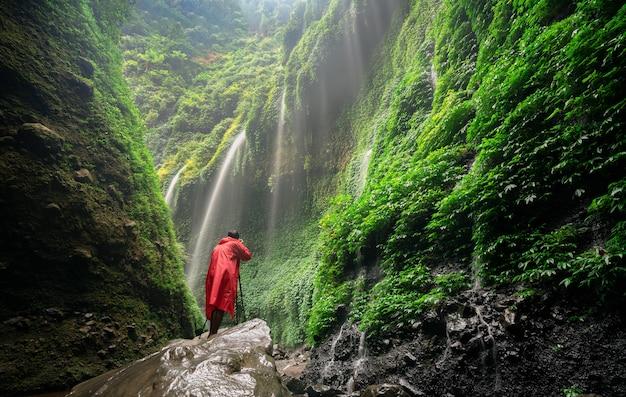 Aventura incrível jovem fotógrafo em pé de casaco de chuva vermelho na pedra e cachoeira