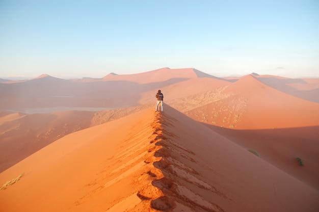Aventura no deserto africano. fotógrafo fazendo fotos de dunas de areia do nascer do sol do deserto do namibe. namíbia, áfrica do sul