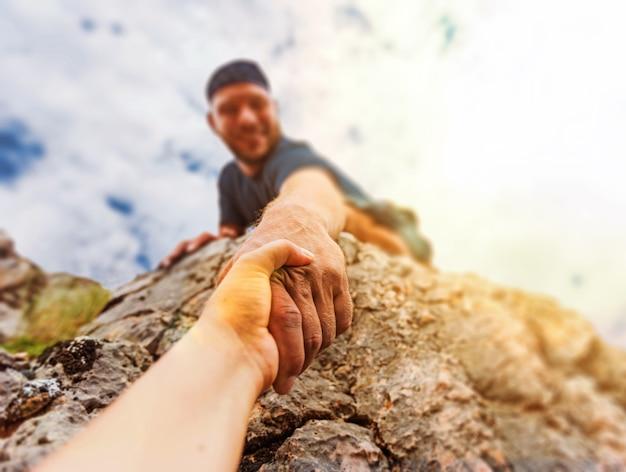Aventureiros ajudando uns aos outros a escalar