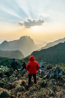 Aventureiros vestindo um moletom vermelho com montanhas e anoitecer perto do pôr do sol no fundo de doi luang chiang dao