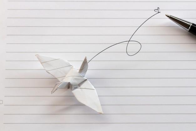 Aves de papel e canetas estão no scrapbook de papel.