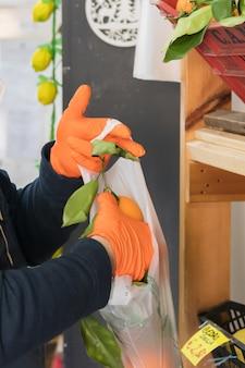 Avetrana, itália - - 16 de março de 2020. uma quitanda italiana está colocando laranja em uma sacola, usando máscara e luvas médicas e respeitando os padrões de saúde durante a epidemia de coronavírus.