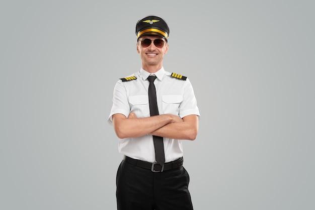 Aviador confiante de uniforme com os braços cruzados