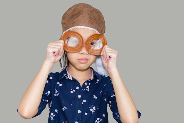 Aviador criança piloto com traçado de recorte em fundo cinza, conceito de jogo de criança feliz