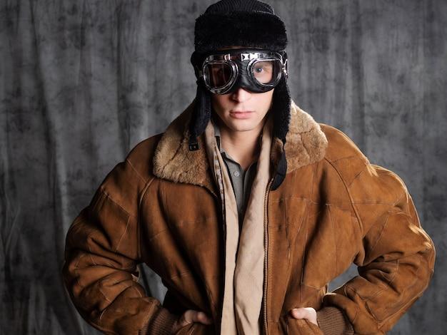 Aviador de estilo retro com um chapéu voador e óculos de proteção no rosto