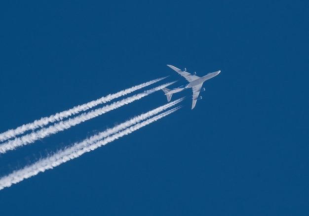 Avião a jato com uma pluma branca em um céu azul