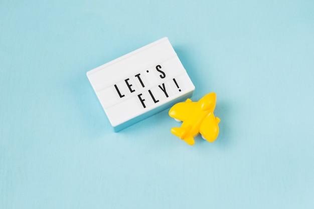 Avião amarelo e uma placa com a frase vamos voar