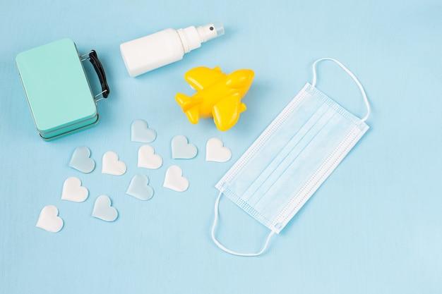Avião amarelo, um desinfetante para as mãos em garrafa, corações de cetim e uma máscara protetora