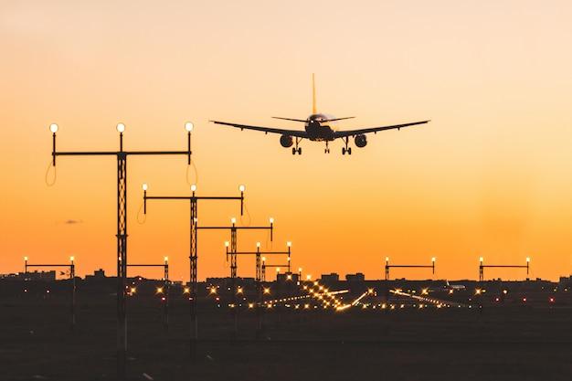 Avião, aterragem, em, pôr do sol, silueta
