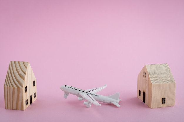 Avião branco e modelo de casa de madeira no fundo rosa para o conceito de viagens