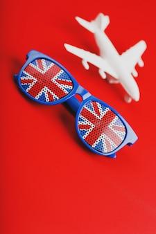 Avião branco e óculos de sol com a bandeira do reino unido. viajar para a inglaterra.
