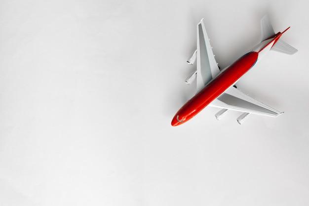 Avião branco vermelho na vista superior de fundo branco com espaço de cópia