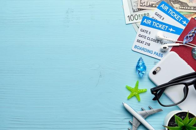 Avião com bilhetes, dinheiro, passaporte, sobre um fundo azul de madeira