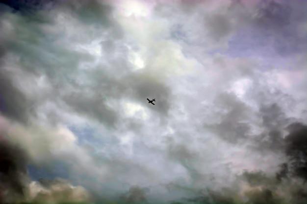 Avião com contrail muito alto no céu entre as nuvens.