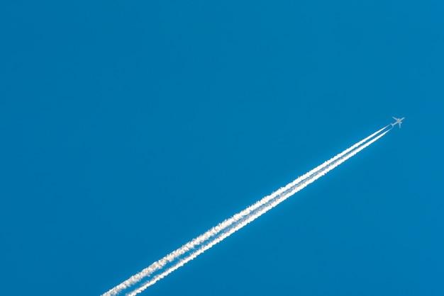 Avião com faixas brancas de condensação. avião a jato no céu azul claro com trilha de vapor. viajar pelo conceito de avião. trilhas dos gases de escape do motor do avião.