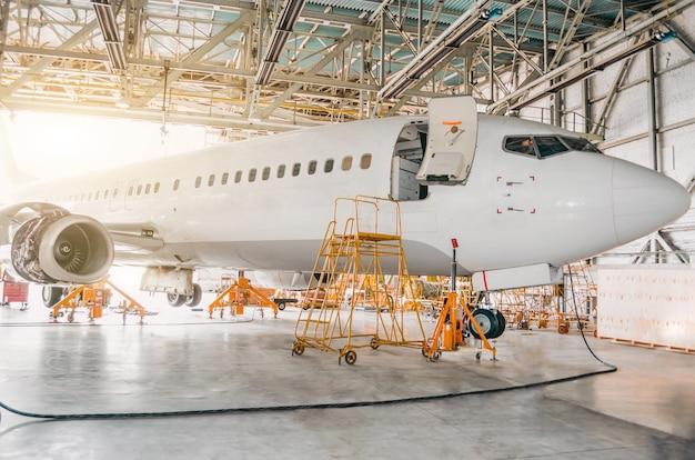 Avião comercial em hangar com portão aberto para o serviço.