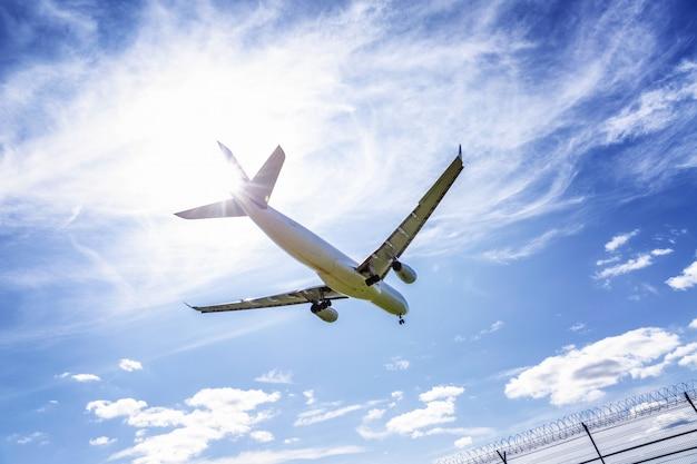 Avião comercial em um céu azul nublado brilhante, close-up.