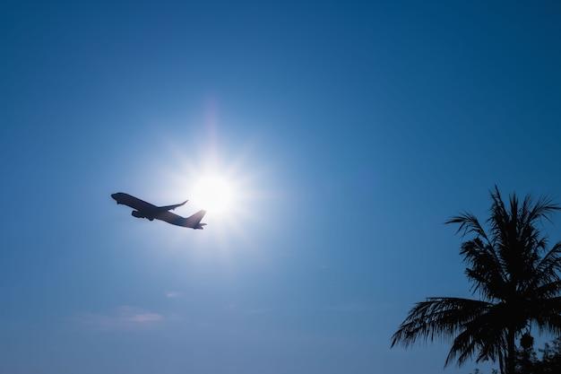 Avião comercial voando acima nuvens através da luz solar e lindo céu azul.