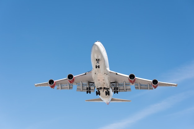 Avião comercial voando no céu azul, aba completa e trem de pouso estendido